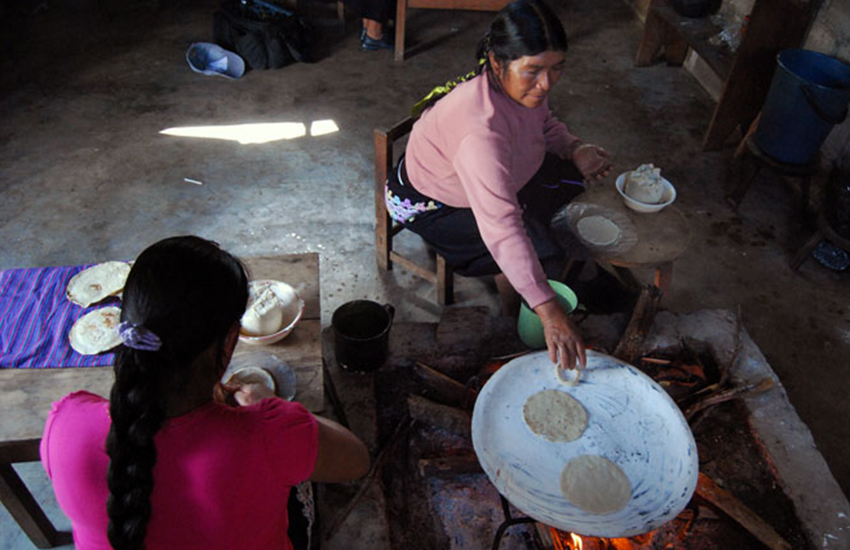 Women make tortillas in a rustic home in Amaquil.