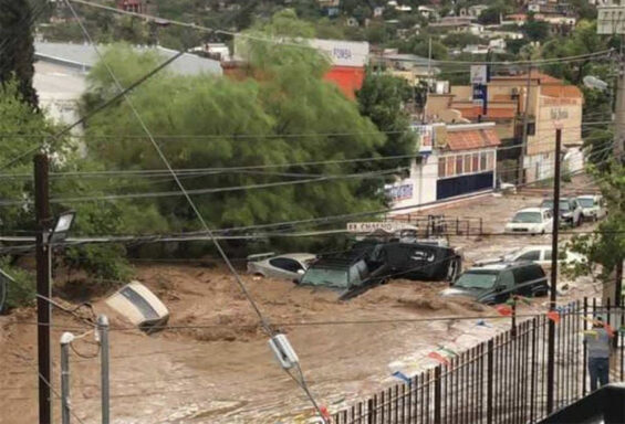 Vehicles are swept away by a river of water on a Nogales street Tuesday.