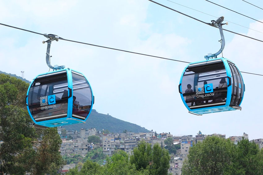 Cablebús cabins carry passengers over Mexico City.