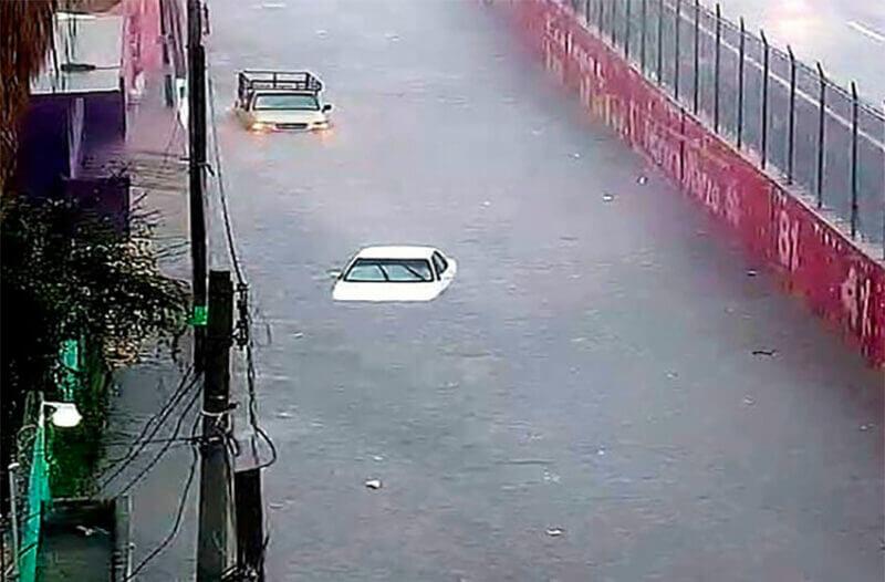 Vehículos casi sumergidos en una calle de Ecatepec.