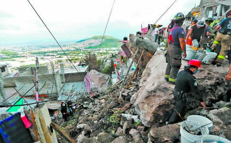 Rescue workers in Tlalnepantla after Friday's slide.